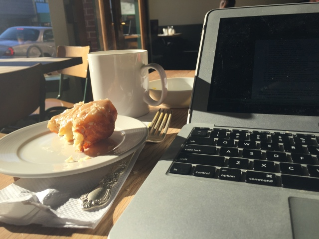 laptop and apple fritter at a cafe